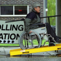 A male wheelchair user pushes up a ramp to access a polling station in the UK