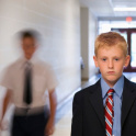 Two school boys in school corridor, one is out of focus, approaching the other who anxiously looks straight into the camera